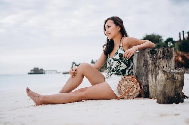 Mujer asiática sentada en la arena blanca junto al océano índico Foto gratis