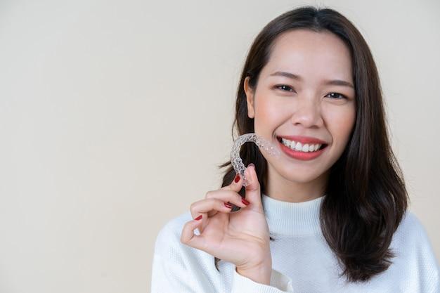 Mujer asiática sonriendo con mano sujetador de alineador dental Foto Premium