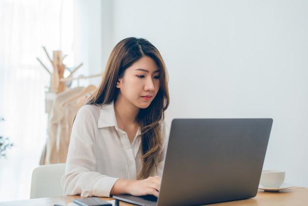 Mujer asiática sonriente de los jóvenes hermosos que trabaja en el ordenador portátil mientras que en casa en espacio de trabajo de oficina Foto gratis