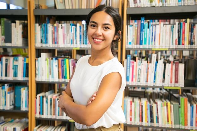 Mujer asiática sonriente que presenta en la biblioteca pública Foto gratis