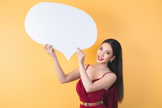 Mujer asiática sosteniendo y mirando a bocadillo con espacio vacío para texto Foto gratis