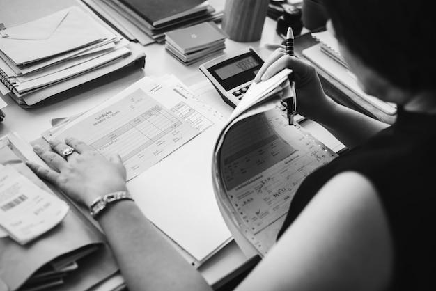 Mujer asiática trabajando a través de papeleo Foto gratis
