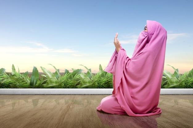Mujer asiática en velo rosa se sienta en posición de oración Foto Premium