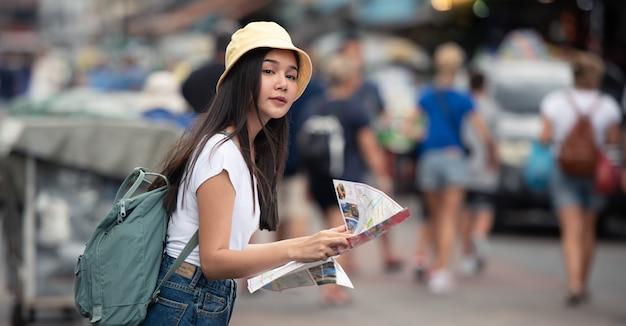 Mujer asiática del viajero en mercado callejero con el mapa, en la ciudad de bangkok de tailandia. Foto Premium