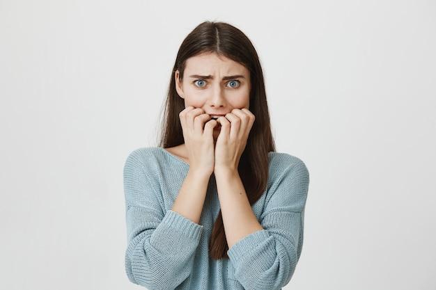 Mujer asustada alarmada mordiéndose las uñas, frunciendo el ceño asustada Foto gratis