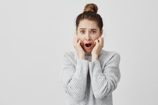 Mujer asustada en suéter gris sosteniendo su mano en las mejillas con la boca abierta aterrorizada. diseñador gráfico femenino preocupado por falta de plazo. concepto de violación Foto gratis