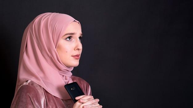 Mujer asustadiza islámica joven que mira lejos sobre el contexto negro Foto gratis