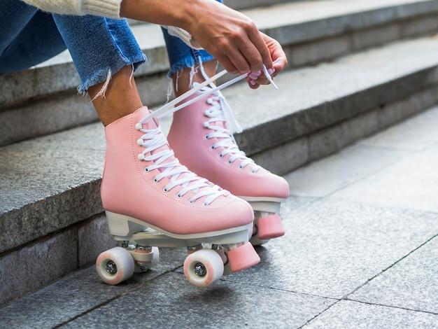 Mujer atar cordones de los zapatos en patines con espacio de copia Foto gratis
