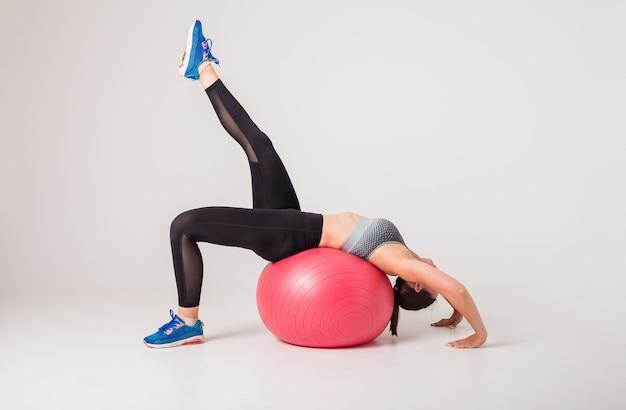 Mujer atleta realiza ejercicios en una pelota de fitness en un blanco aislado con espacio para texto Foto Premium