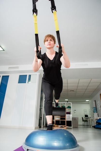 La mujer atlética hace ejercicio trx Foto Premium