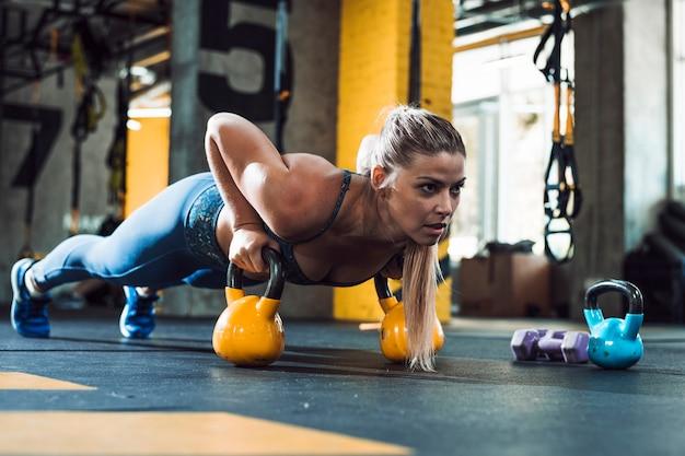 Una mujer atlética haciendo flexiones en bola de caldera Foto gratis