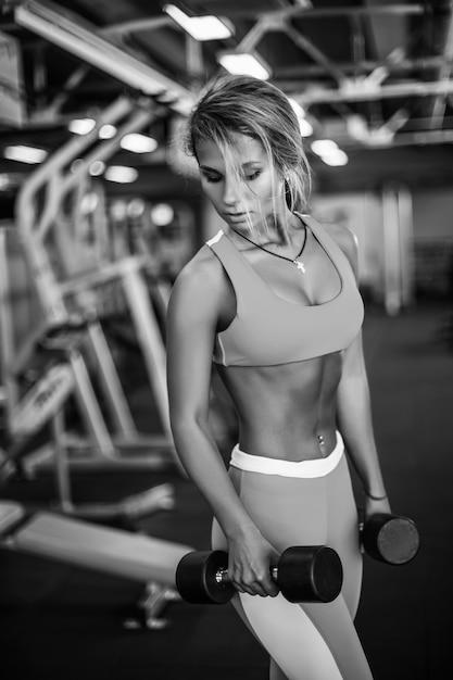 Mujer atlética joven de la aptitud que ejercita en gimnasio Foto Premium