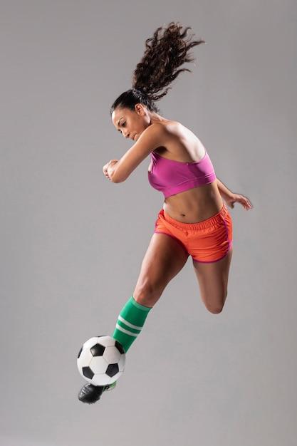 Mujer atlética pateando fútbol Foto gratis