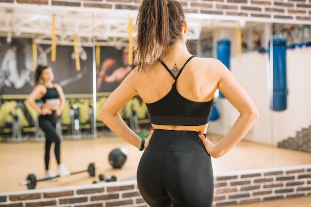 Mujer atlética de pie cerca de pesas y espejos Foto gratis