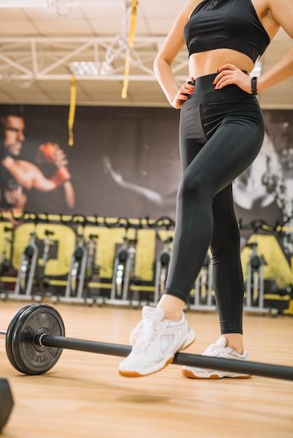 Mujer atlética de pie cerca de pesas Foto gratis