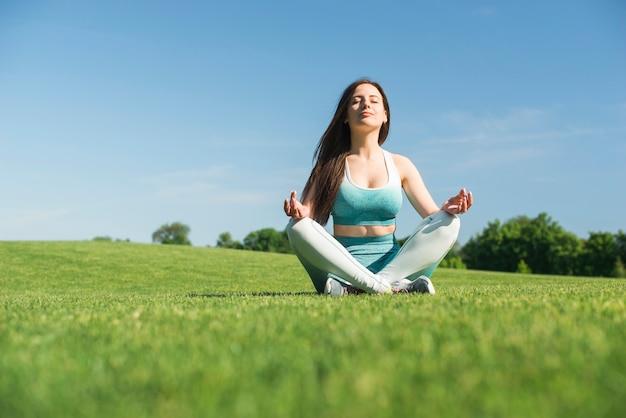 Mujer atlética practicando yoga al aire libre Foto gratis