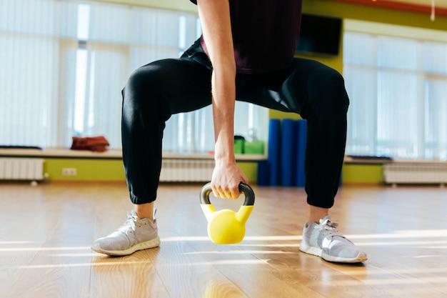 Mujer atlética que ejercita con la campana de la caldera mientras que está en la posición agazapada. mujer muscular que hace entrenamiento cruzado del ajuste en el gimnasio. Foto Premium