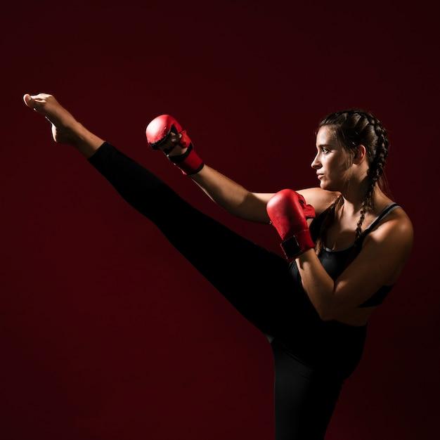 Mujer atlética en ropa de fitness dando una patada Foto gratis