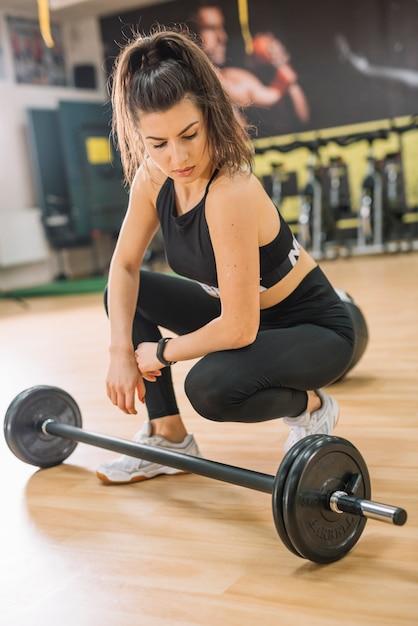 Mujer atlética sentada cerca de pesas Foto gratis