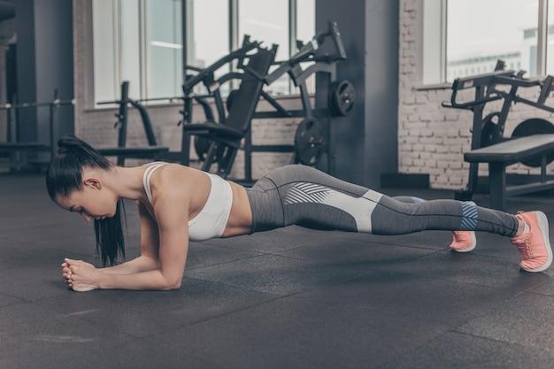 Mujer atlética en sujetador deportivo y polainas haciendo ejercicio de tabla en el gimnasio, espacio de copia Foto Premium
