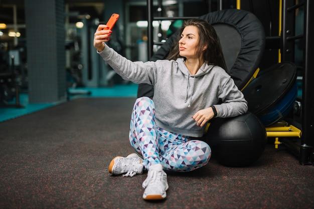 Mujer atlética tomando selfie en smartphone en gimnasio Foto gratis