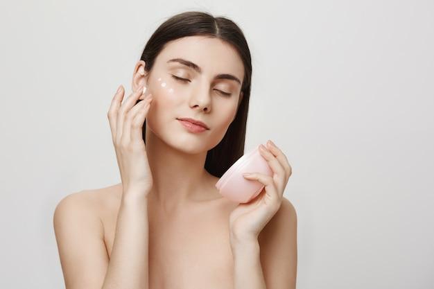 Mujer atractiva aplicar crema facial, producto anti-envejecimiento Foto gratis