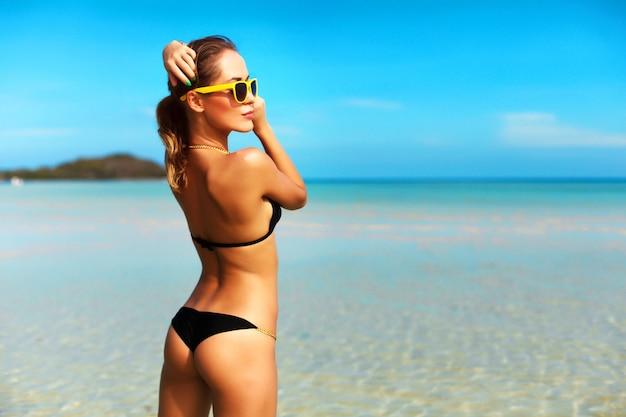 d4d65803dc39 Mujer atractiva con bañador negro y gafas de sol amarillas ...