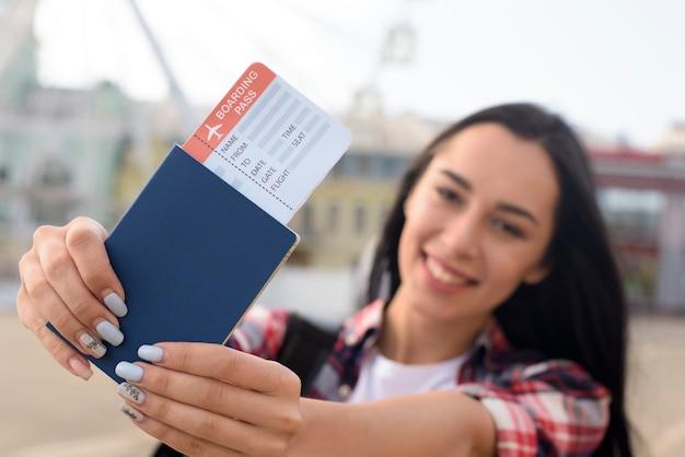 Mujer atractiva feliz mostrando pasaporte y boleto aéreo al aire libre Foto gratis