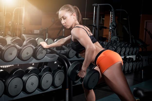 Mujer atractiva en forma trabaja con pesas en el gimnasio Foto gratis