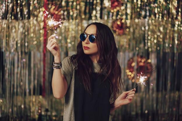 Mujer atractiva hipster con bengalas en las manos Foto gratis