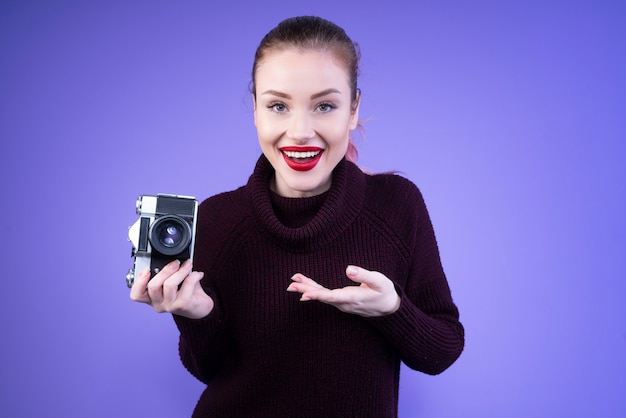 Mujer atractiva en jersey de punto nos muestra su nueva cámara Foto gratis