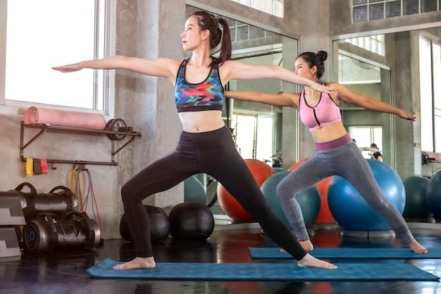 Mujer atractiva joven de asia y amigo que se extiende en el gimnasio. Foto Premium