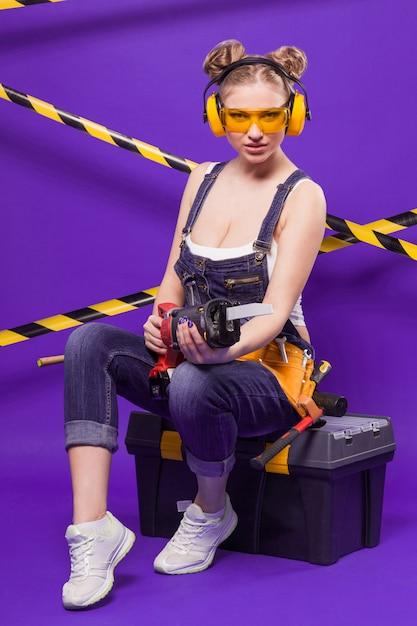 Mujer atractiva joven constructor en traje de mezclilla y gafas sentado en caja de herramientas negra Foto Premium