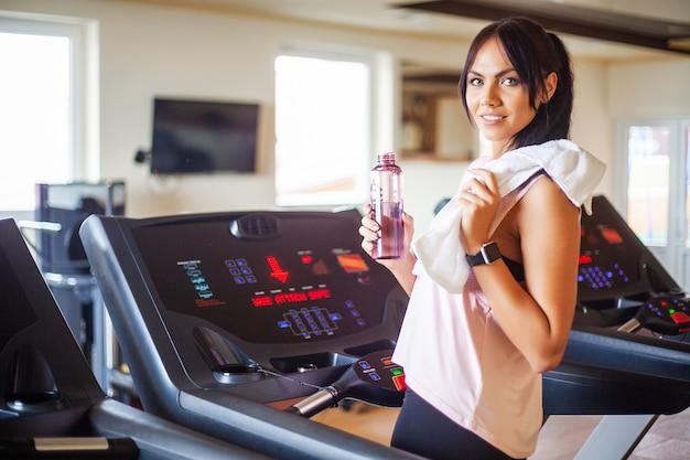 Mujer atractiva joven fitness correr en cinta rodante, vistiendo ropa deportiva blanca, mujer deportiva sana haciendo ejercicio cardiovascular en cinta Foto Premium