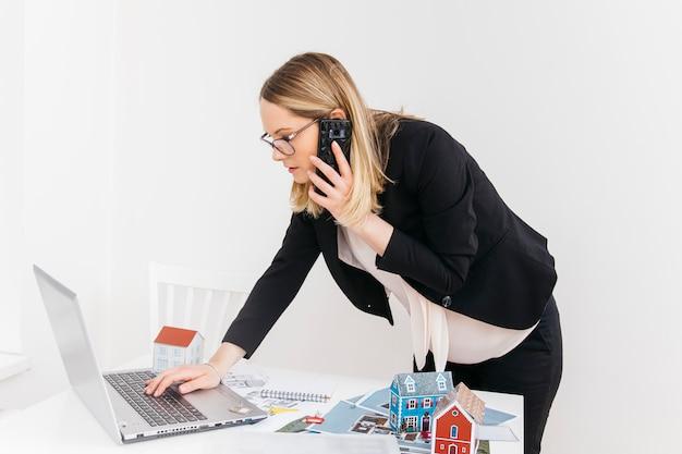 Mujer atractiva joven que habla en el teléfono celular mientras trabaja en la computadora portátil en la oficina de bienes raíces Foto gratis