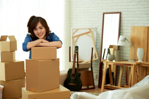 Mujer atractiva joven que se inclina sobre una pila de cajas de paquetes sonriendo Foto gratis