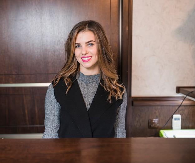 Mujer atractiva joven sonriente que se sienta en el escritorio en el hotel Foto gratis
