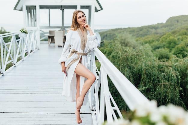 Mujer atractiva, joven con teléfono en las manos en la terraza de verano en las montañas. tiempo de belleza. concepto de mañana Foto Premium