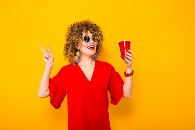Mujer atractiva con pelo corto y rizado y bebida. Foto Premium