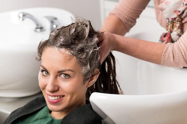Mujer atractiva que se lava el pelo Foto Premium