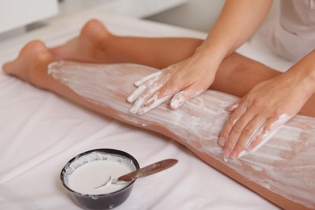 Mujer atractiva recibiendo envolturas corporales con máscara en el centro de spa Foto Premium