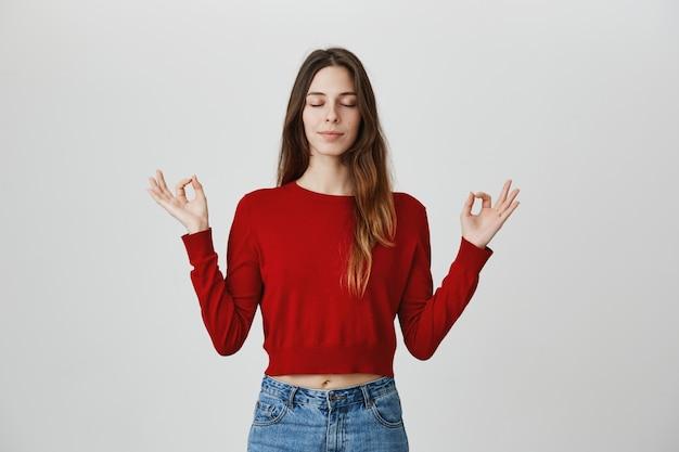 Mujer atractiva relajada y tranquila meditando con las manos abiertas hacia los lados, los ojos cerrados, hacer yoga Foto gratis