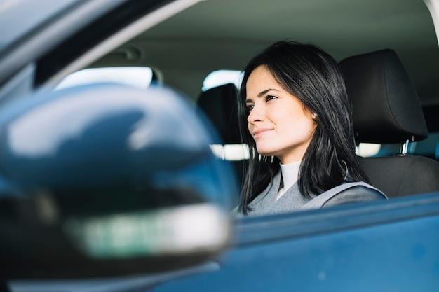 Mujer atractiva sentada en coche Foto gratis