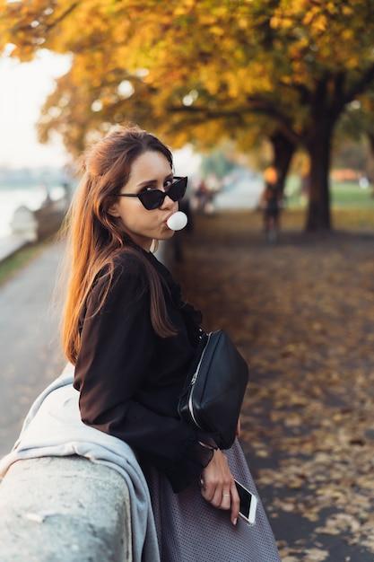 Mujer atractiva con smartphone al aire libre en el parque Foto gratis