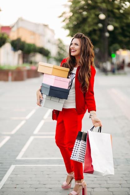 Mujer atractiva sonriente en traje elegante del deporte rojo que sostiene las cajas de zapatos y los panieres en la calle. Foto Premium