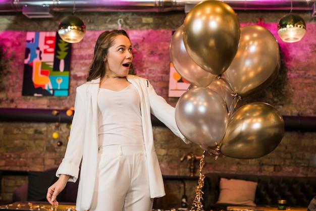 Mujer atractiva sorprendida mirando globos de plata en bar Foto gratis