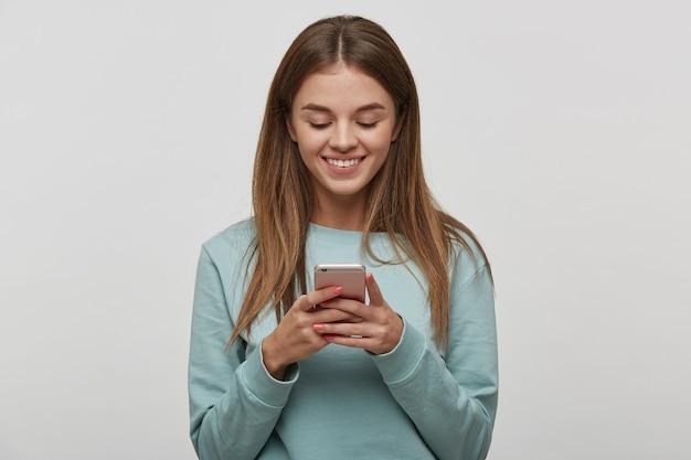 Mujer atractiva sosteniendo teléfono móvil y escuchando música Foto gratis