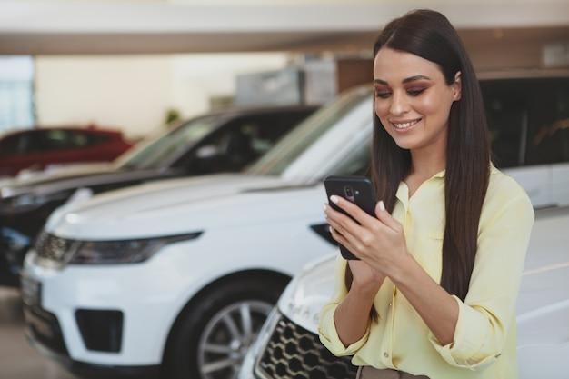 Mujer atractiva usando su teléfono inteligente mientras está en auto nuevo Foto Premium