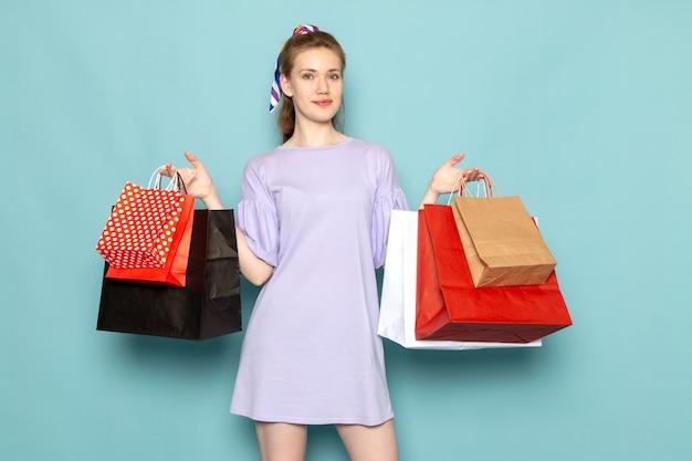 Una mujer atractiva de vista frontal en camisa-vestido azul sosteniendo paquetes de compras en azul Foto gratis
