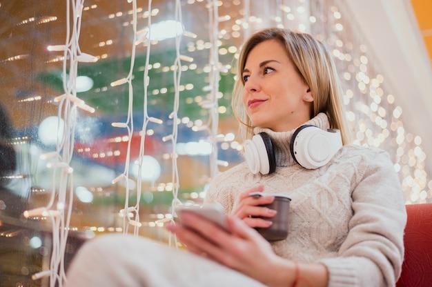Mujer con auriculares alrededor del cuello y la copa cerca de las luces de navidad Foto gratis